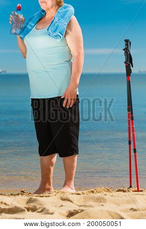 Senior woman practicing nordic walking on sea shore drinking fresh water after activity. Elderly female enjoying sunny summer day. Healthy active retirement age.