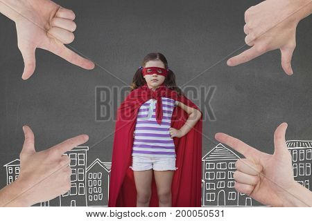 Digital composite of Hands pointing at girl in a super heroine custom against grey background with city illustration