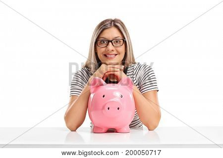 Young woman with a piggybank sitting at a table isolated on white background