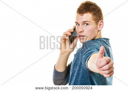 Technology and communication. Young man casual style talking on mobile cell phone using smartphone making thumb up hand sign gesture isolated on white