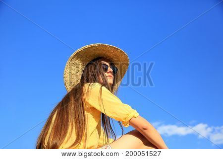 Beautiful girl in background of the blue sky