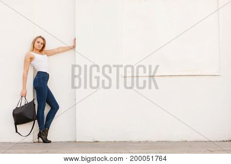 Female fashion - urban style. Young attractive trendy woman model posing outdoor with black bag in hand.