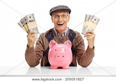 Cheerful senior with bundles of money and a piggybank sitting at a table isolated on white background
