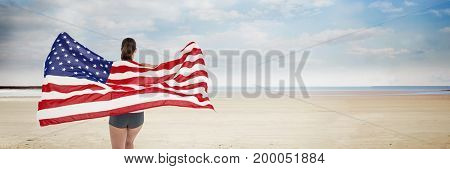 Digital composite of Woman holding USA flag against beach background