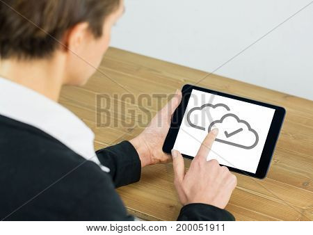 Digital composite of Cloud tick icons on tablet with hand