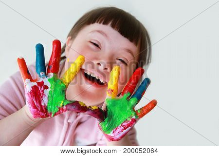 Cute little down syndrome girl with painted hands