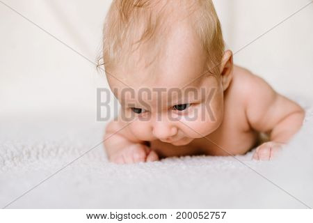 The two-month boy trying to lift his head lying on his stomach