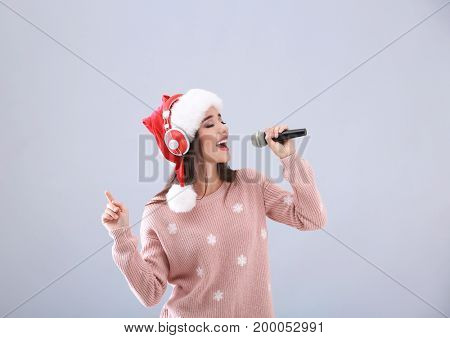 Beautiful young woman in Santa hat singing Christmas songs on light background