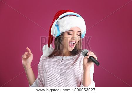 Beautiful young woman in Santa hat singing Christmas songs on color background
