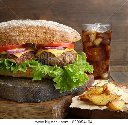 Big and tasty hamburger on desk with cola and fried potatoes on dark background