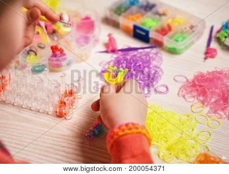 extracurricular activities, group, education and handwork concept - hands weaving of colored rubber band bracelet, closeup, wooden background