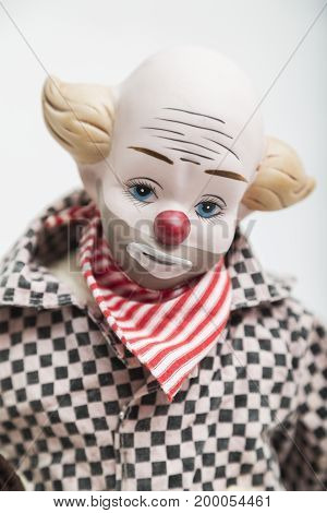 Ceramic porcelain handmade vintage doll of sad clown with blue eyes, red nose, blond hair, half bold in plaid black and white shirt, red bandanna bandage around the neck on white background.