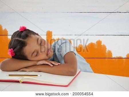 Digital composite of Schoolgirl asleep at desk with painted orange background