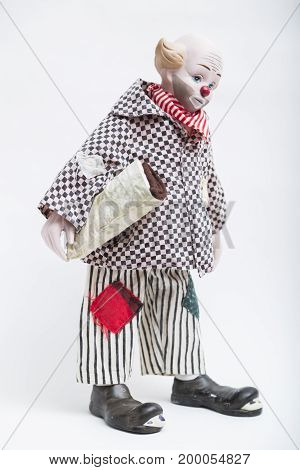 Ceramic porcelain handmade vintage doll of sad abdominous clown with red nose, blond hair, half bold in plaid black and white shirt, striped pants with patches, ragged shoes on white background.
