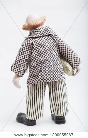 Ceramic porcelain handmade vintage doll of no face clown with blond hair, half bold in plaid black and white shirt, striped pants, black ragged shoes with on white background.
