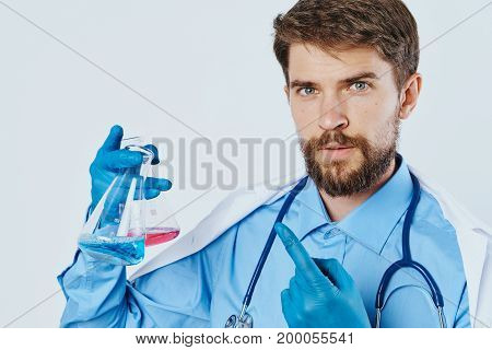 Man with a beard on a light background holds laboratory utensils, science, doctor, portrait, scientist, medicine.