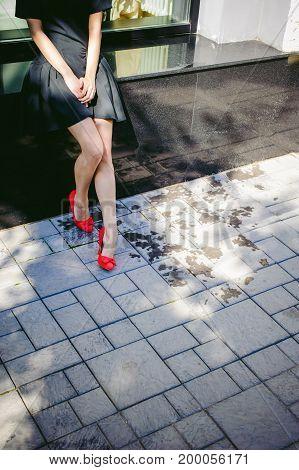 Beautiful Woman In A Dark Stylish Dress Strolls Along The Street, Near Boutiques. Slender Legs In Re
