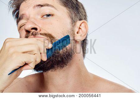 Man on a light background combs beard comb, portrait.