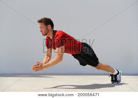 Clap pushup fitness man doing plyometric push-up explosive workout for muscles training. Athlete working out on gym floor.