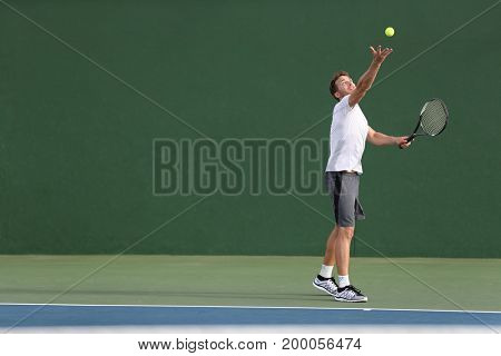 Tennis serve player man serving ball during match point on outdoor green court. Athlete playing sport game training doing exercise.