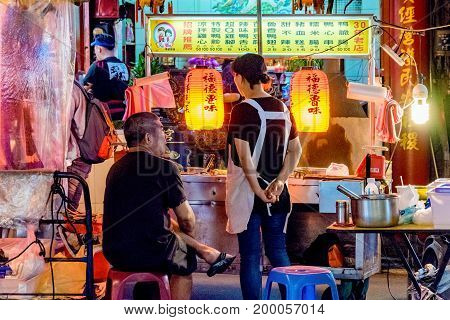 TAIPEI TAIWAN - JUNE 19: This is a night scene of a street vendor in the Raohe street night market. These kinds of vendors are very popular with locals and tourists on June 19 2017 in Taipei