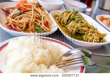 thai cuisine Grilled pork Thai papaya salad also known as Som Tum from Thailand and Spicy Bamboo Shoot Salad