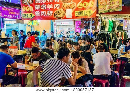 TAIPEI TAIWAN - JUNE 19: This is a night scene of people eating in Raohe street night market a famous market where many locals and tourists come to eat and shop on June 19 2017 in Taipei