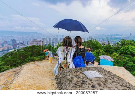 TAIPEI TAIWAN - JUNE 11: This is the peak of Battleship rock which is a popular mountain in Taipei. Tourists watch the view as it begins to rain on June 11 2017 in Taipei