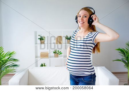 Pregnant woman listening to music in headphones