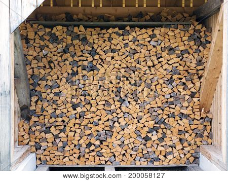 Chopped wood straightened in row. Wooden logs for heating. Wall made of cut logs. Fuel for fireplace and stove. Natural wooden texture. Stock of logs for winter heating. Rustic rural scene.