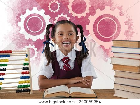 Digital composite of Schoolgirl reading at desk in front of settings gear cogs