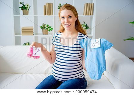 A portrait of a pregnant woman with baby clothes