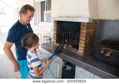 grandfather makes a barbecue with his granddaughter