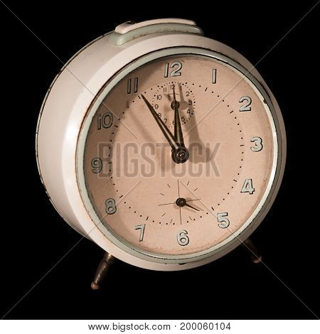 Old alarm clock five to twelve on black background