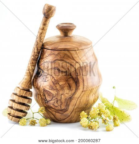 Wooden pot full of fresh linden honey and linden flowers.
