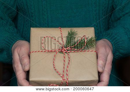 Man's hand hold christmas or new year gift box with red ribbon in white sweater.
