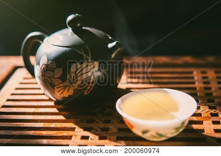 Chinese tea ceremony. Teapot and a cup of green puer tea on wooden tabl with small amount of vapour. Asian traditional culture