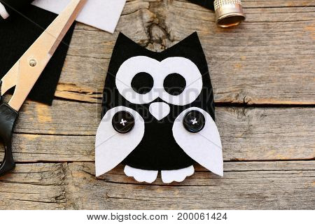 Stuffed felt owl ornament on a vintage wooden background. Making adorable owl ornament from black and white felt. DIY felt projects. Top view