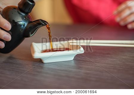 Japanese food soy sauce poured into a plate and next to lie wooden sticks