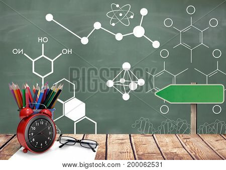 Digital composite of Desk foreground with blackboard graphics of science