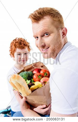 happy redhead father and son holding full grocery bag and smiling at camera isolated on white