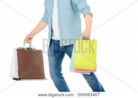 cropped shot of man holding colorful shopping bags isolated on white