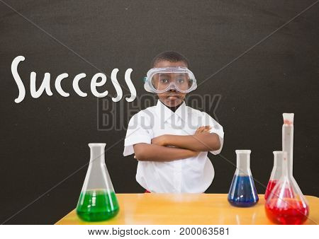 Digital composite of Student boy at table against grey blackboard with success text