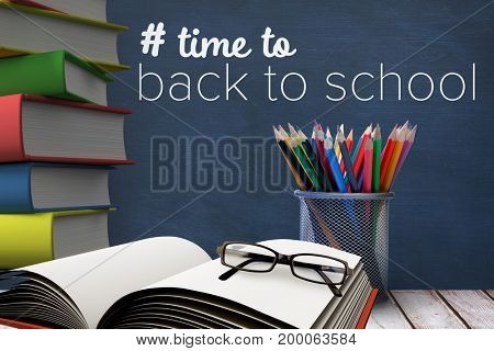 Digital composite of Books on the table against blue blackboard with back to school text