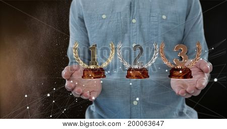 Digital composite of Man with trophies on hands