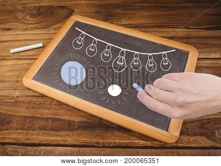 Digital composite of Hand drawing light bulbs and sun shining on blackboard