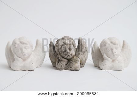 Three small identic handmade decorative stone gyps lying sad boys children angels in studio on white background.
