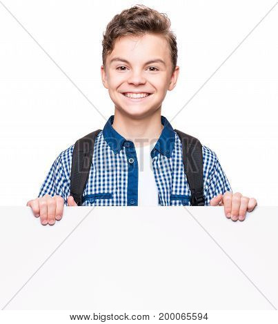 Portrait of handsome teen boy posing behind white panel isolated on white background. Teenager child holding empty billboard. Young student with school bag peeping behind blank board.