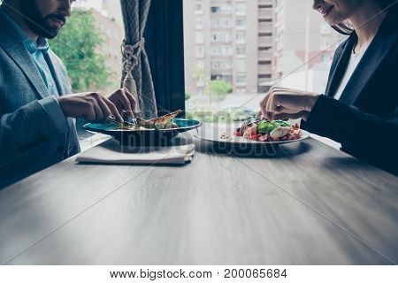 Brunch together. Low angle of two young business partners are sitting in a fancy restaurant wearing smart outfits and eating delicious salads smiling enjoying