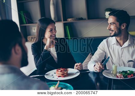 Young Married Couple Of Business People And Their Colleague Are Having Brunch Together In A Cafe, Fr